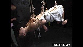 天井から伸びる縄に吊し上げされた奴隷女、体に熱々のロウソクを垂らされ悲鳴のような喘ぎ声をあげる