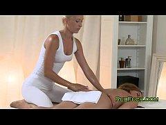 Blonde masseuse massages naked brunette