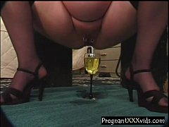 Pregnant Wife fills a glass with piss