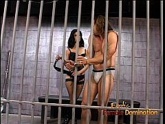 Hot raven-haired domina Leah Wilde sits on a hu...