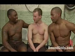 Two black boys on a tied up guy