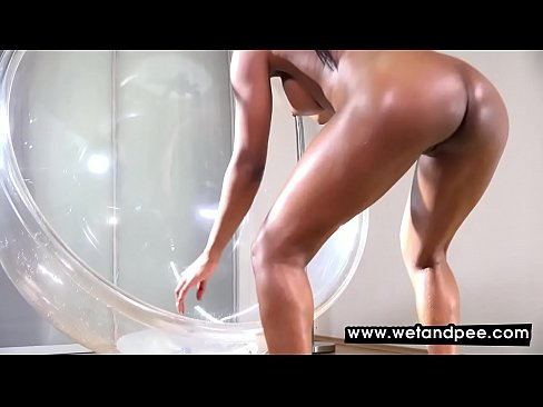 Ebony babe pees in a glass chair