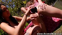 Lesbo hotties enjoy outdoor milk enemas
